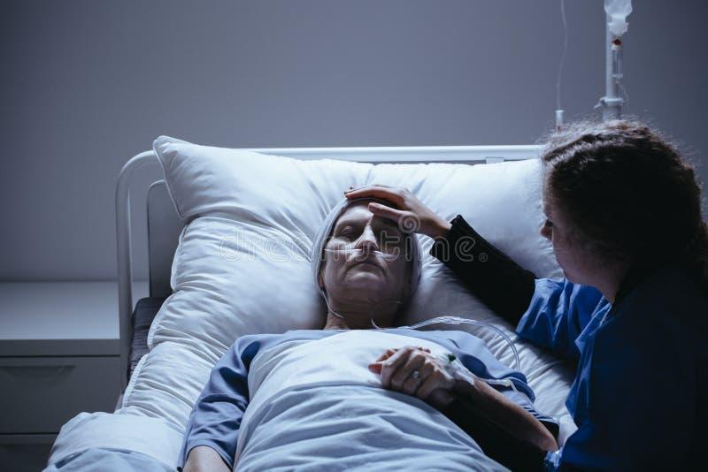 Figlia preoccupata che prende cura della madre anziana debole con cancro immagini stock