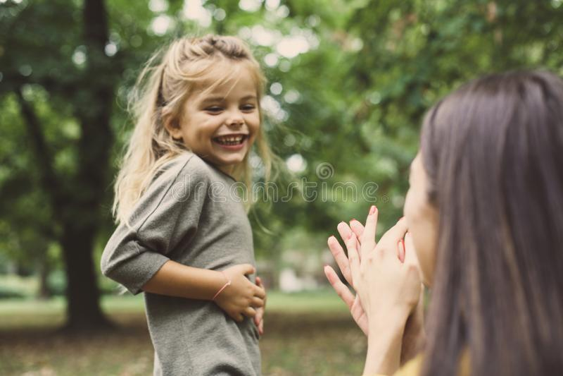 Figlia sorridente che gioca con la mamma Fuoco sulla bambina immagini stock