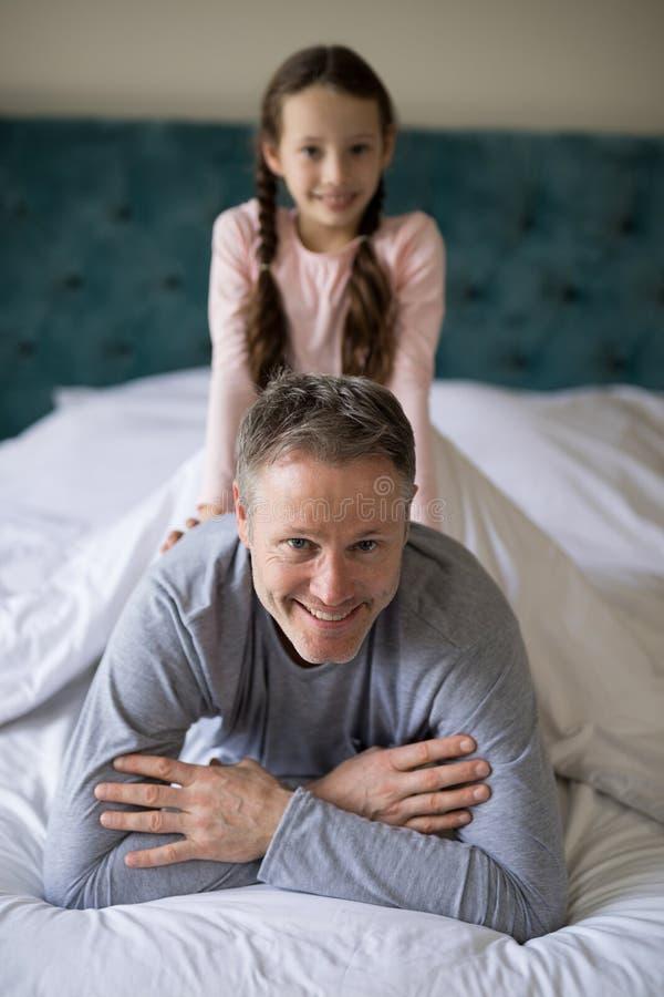 Figlia sorridente che si siede sui padri indietro nella camera da letto fotografia stock libera da diritti