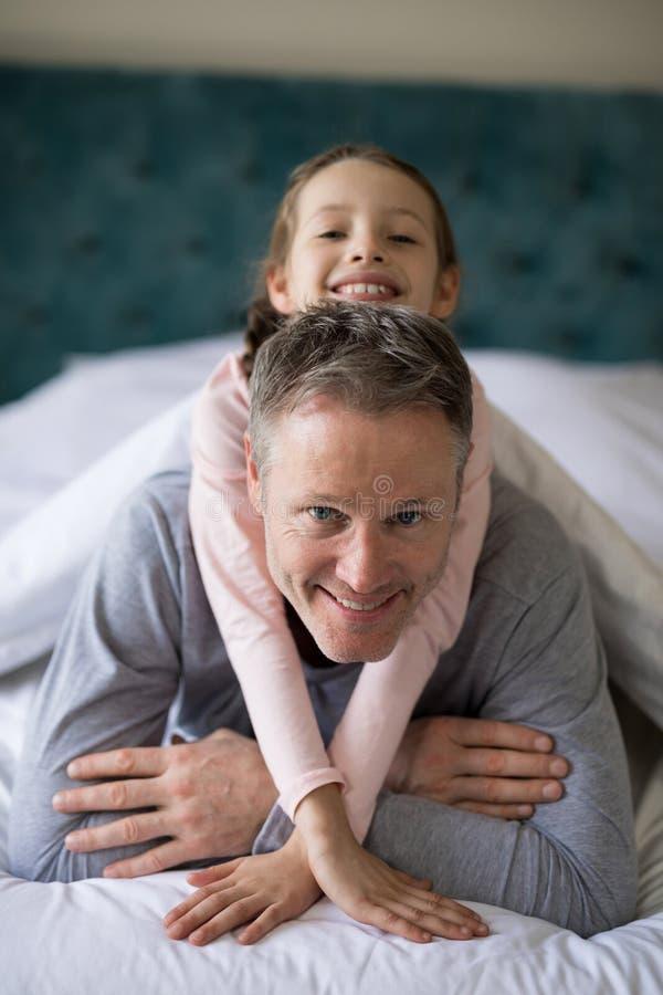 Figlia sorridente che si trova sui padri indietro nella camera da letto immagini stock