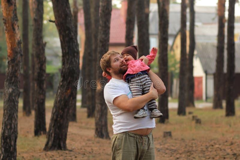 Figlia stringente a sé del bambino e del padre che ride nel parco immagini stock libere da diritti