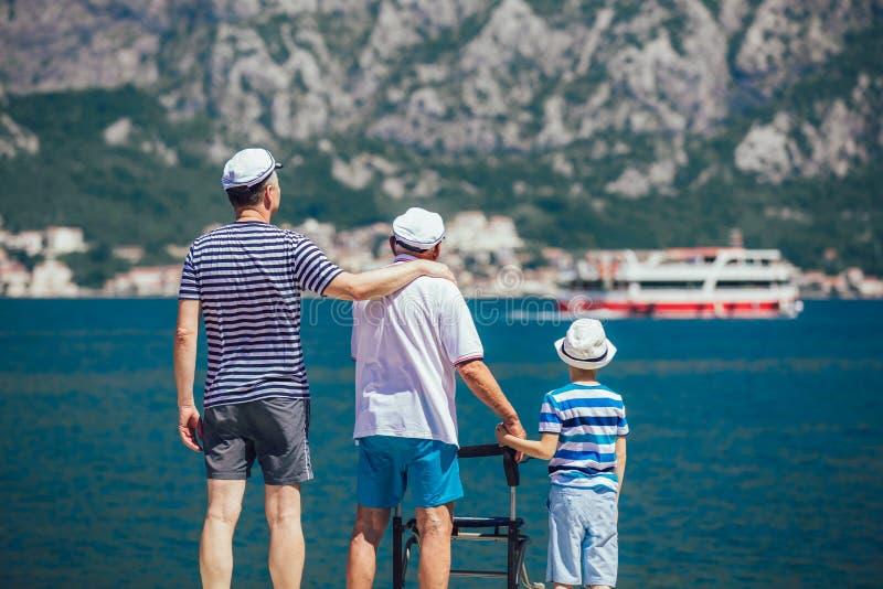 Figlio adulto e nipote del padre anziano fuori per una passeggiata al mare fotografia stock
