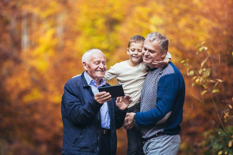 Figlio adulto e nipote del padre anziano fuori per una passeggiata nel parco, facendo uso della compressa digitale fotografia stock