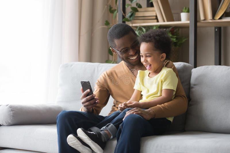 Figlio africano felice del bambino e del papà che ride esaminando cellulare immagine stock libera da diritti