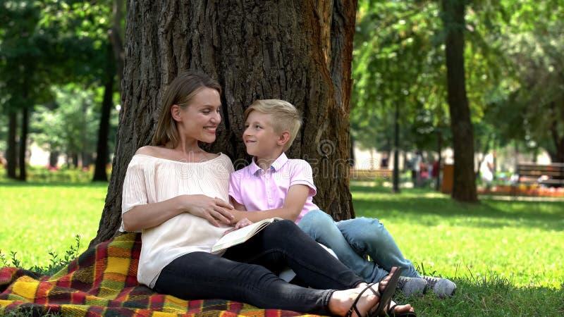 Figlio allegro che tocca la pancia incinta della madre, fratello aspettante del bambino, felicità immagini stock libere da diritti