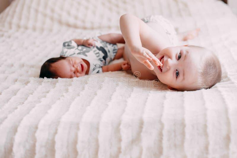 figlio biondo del ragazzo del fratello maggiore che gioca con la piccola sorella del bambino immagine stock