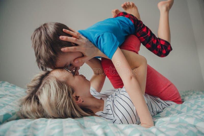 Figlio caucasico del ragazzo e della madre che gioca nella camera da letto a casa fotografia stock libera da diritti