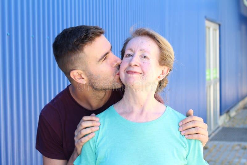 Figlio che bacia il suo ritratto della madre fotografia stock