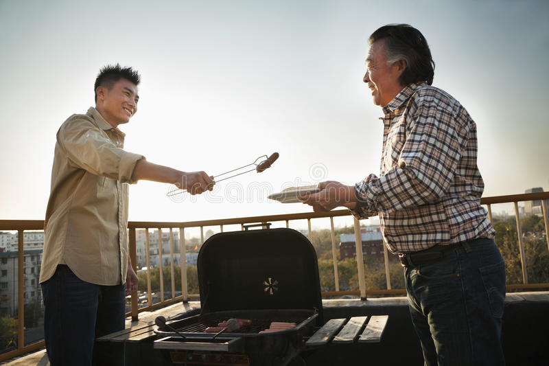 Figlio che dà salsiccia a suo padre sopra il barbecue fotografia stock