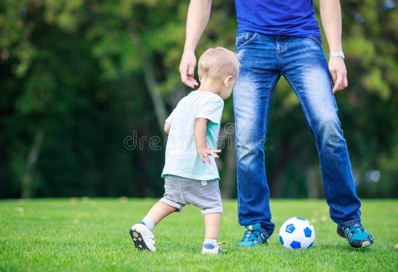 Figlio del bambino e dell'uomo che gioca a calcio nel parco immagini stock libere da diritti