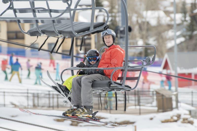 Figlio del bambino & del padre sicuro su Ski Lift ad una località di soggiorno di montagna di Colorado con Ski Area nei precedent immagini stock libere da diritti