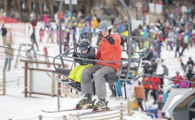 Figlio del bambino & del padre su Ski Lift ad una località di soggiorno di montagna di Colorado con le folle della gente nei prec fotografie stock libere da diritti