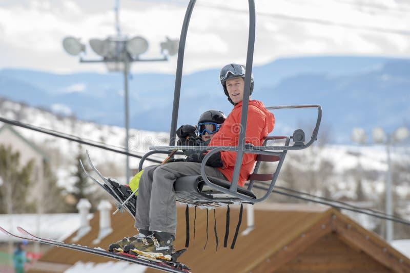 Figlio del bambino & del padre su Ski Lift con la località di soggiorno di montagna di Snowy Colorado nei precedenti fotografie stock