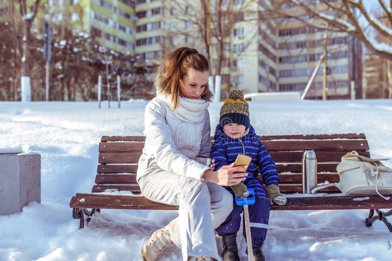 Figlio del ragazzino 2-3 anni, banco di seduta nella città di inverno Mamma della donna in mani del telefono, prendenti le immagi immagini stock