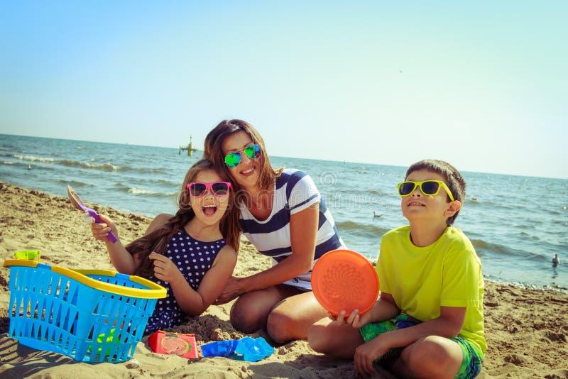 Figlio della figlia della madre della famiglia divertendosi sulla spiaggia fotografia stock