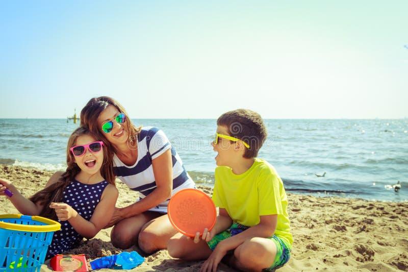 Figlio della figlia della madre della famiglia divertendosi sulla spiaggia immagini stock libere da diritti