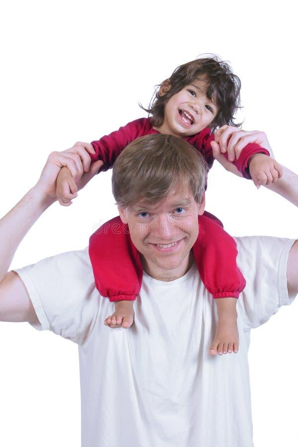 Figlio di trasporto del padre sulle sue spalle fotografia stock