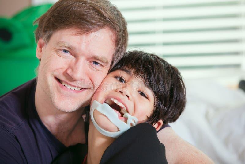 Figlio disattivato tenuta sorridente del padre fotografia stock libera da diritti