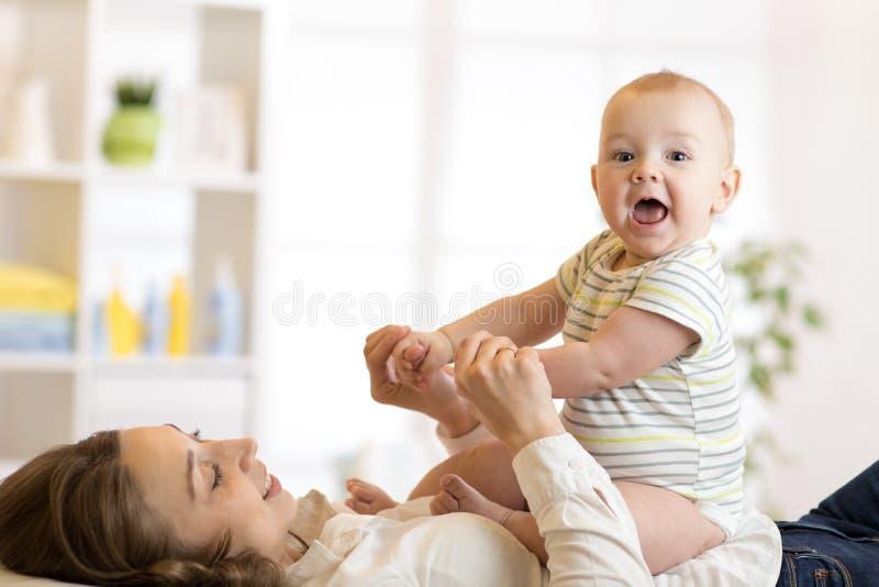 Figlio sveglio del bambino che si siede sulla sua mamma felice che si trova sul pavimento a casa immagini stock libere da diritti