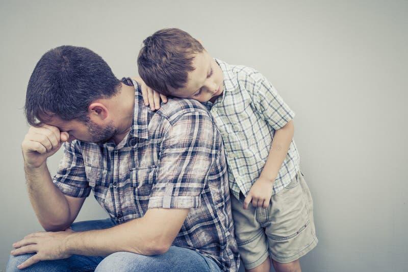 Figlio triste che abbraccia il suo papà vicino alla parete fotografie stock libere da diritti
