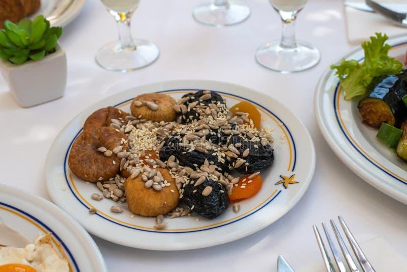 Figos, ameixas secas e sementes e outro de girassol na placa - conceito saudável do café da manhã imagem de stock