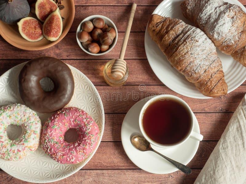 Figos do croissant da filhós do café da manhã nuts nas placas e no copo de chá na tabela imagem de stock royalty free