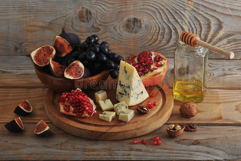 Figos e uvas do preto em uma bacia de madeira fotografia de stock royalty free