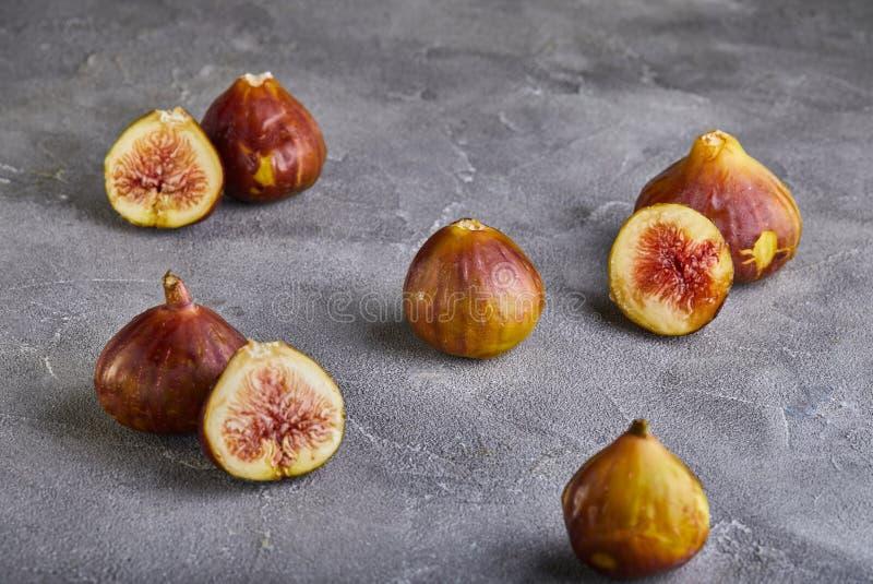 Figos frescos inteiros e para cortar em partes em um fundo cinzento, o conceito de um saudável foto de stock royalty free