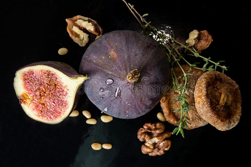 Figos, figos secados, metade do figo, noz e pinhões no CCB preto imagem de stock royalty free