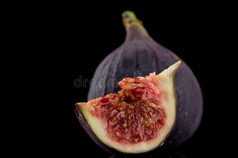 Figos Uma fatia de figo e de um figo inteiro no fundo preto, macro imagens de stock