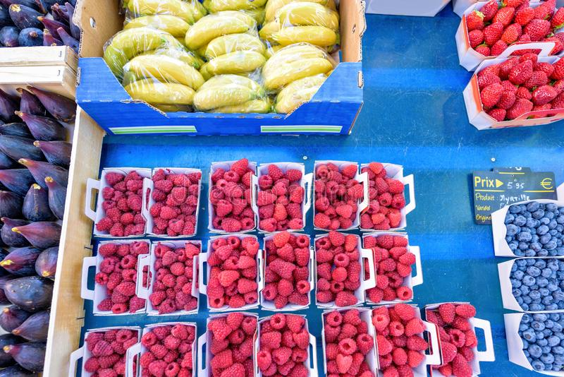 Figs, bananas, raspberries, blueberries and strawberries in boxes for sale. In local marketplace royalty free stock photo