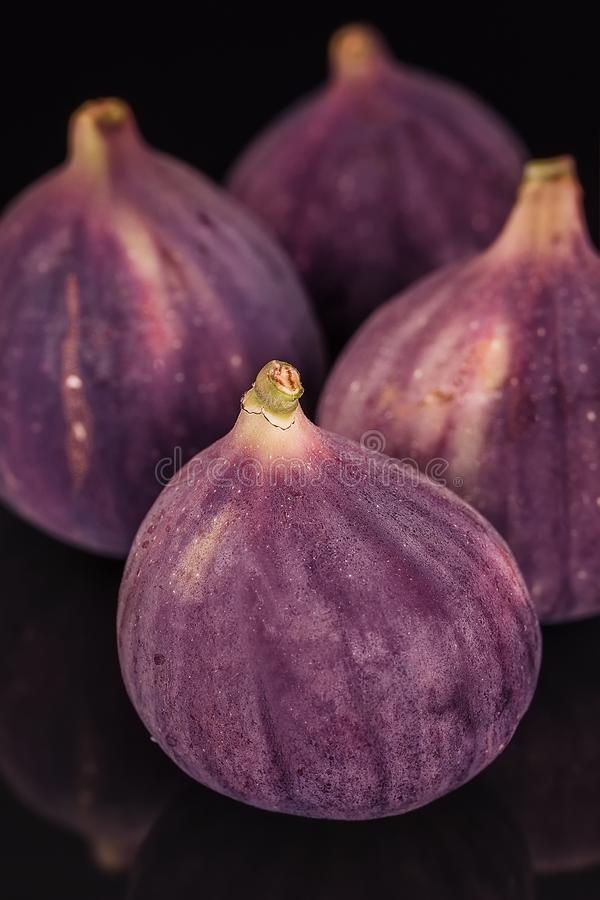 Figs fresh beautiful violet four pieces on a black glass background, close-up. Selective focus royalty free stock photo