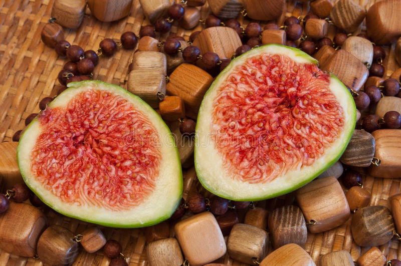 Figs, halved fig. Halved fig on wooden beads background royalty free stock photo