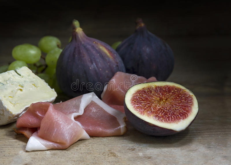 Figs with ham and cheese on rustic wood, food still life. Figs with ham and cheese on a rustic wooden table, food still life with selected focus, narrow depth of stock photos