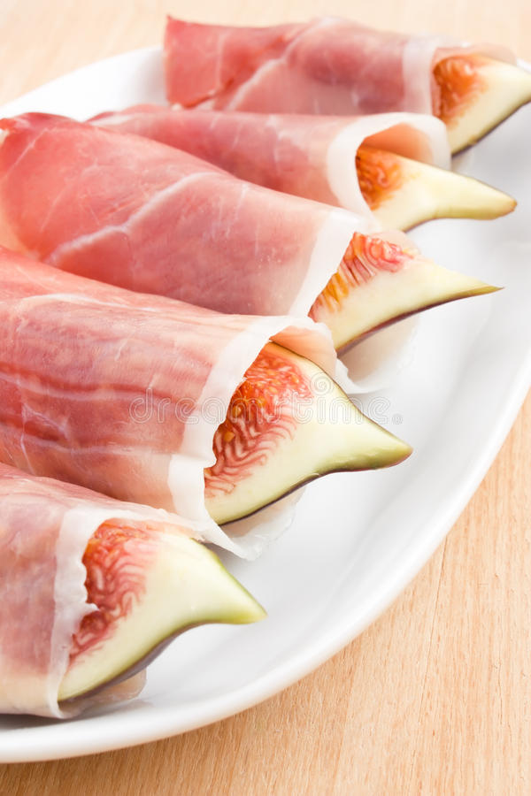 Figs in Prosciutto Italian cured ham. Slices of figs in Prosciutto Italian cured ham royalty free stock images