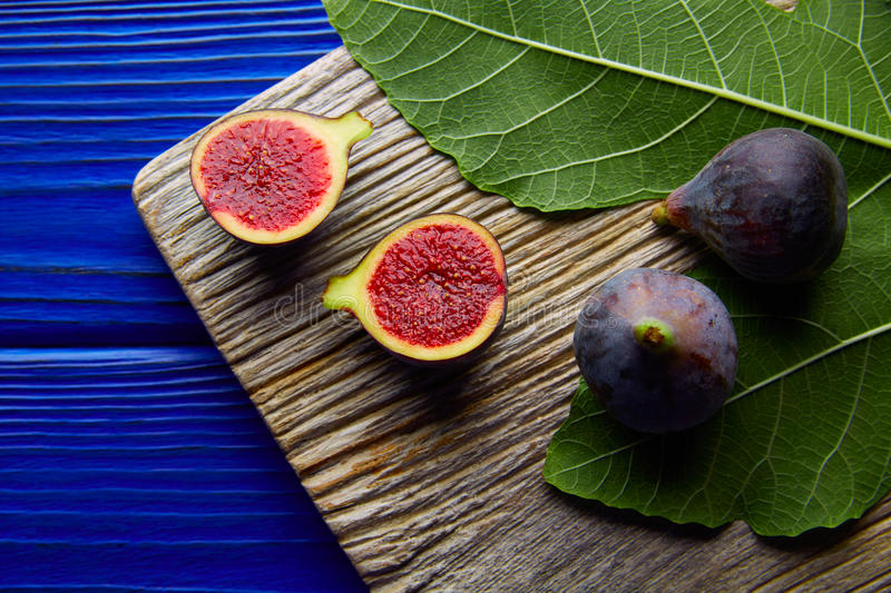 Figs raw cutted fruits and fig tree leaves on blue. Wooden table stock images