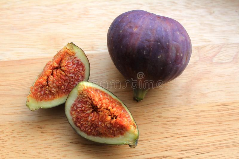 Figs on the wooden desk. Ficus carica is an Asian species of flowering plant in the mulberry family, known as the common fig. It is the source of the fruit also stock photo