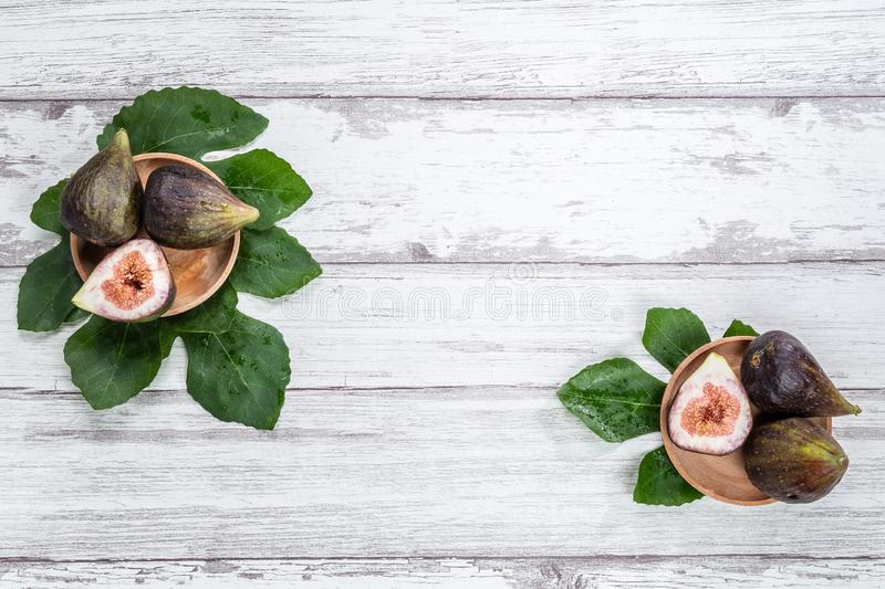 Figs on wooden plates and fig leaves. White wood background. Top view.  royalty free stock photos