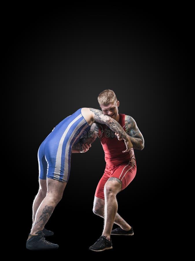 Figting di due lottatori di stile libero isolato su fondo nero fotografia stock libera da diritti