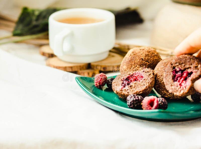 Figues de chocolat de truffes, baies fra?ches et avocats Boule saine faite maison de sucrerie de vegan dans les mains d'une jeune image libre de droits