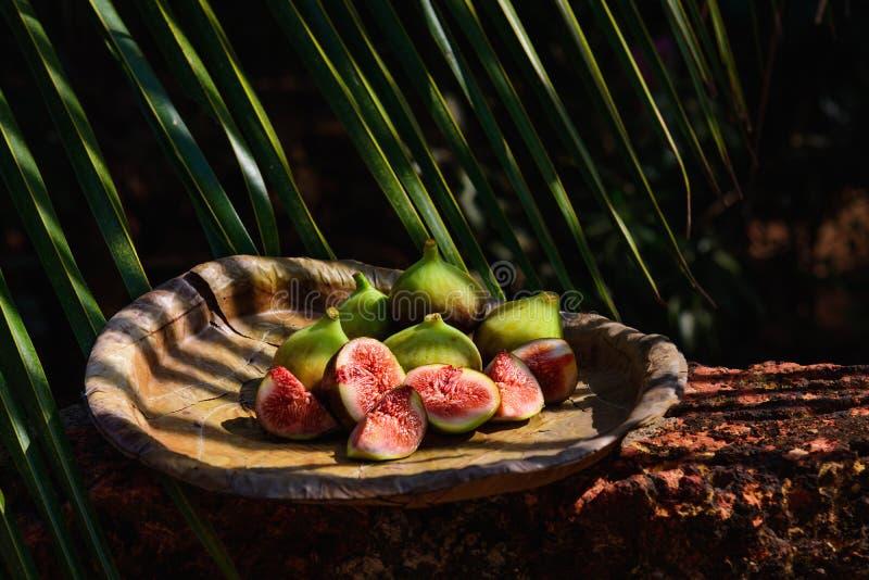 figues fraîches d'un plat naturel sous la paume image stock