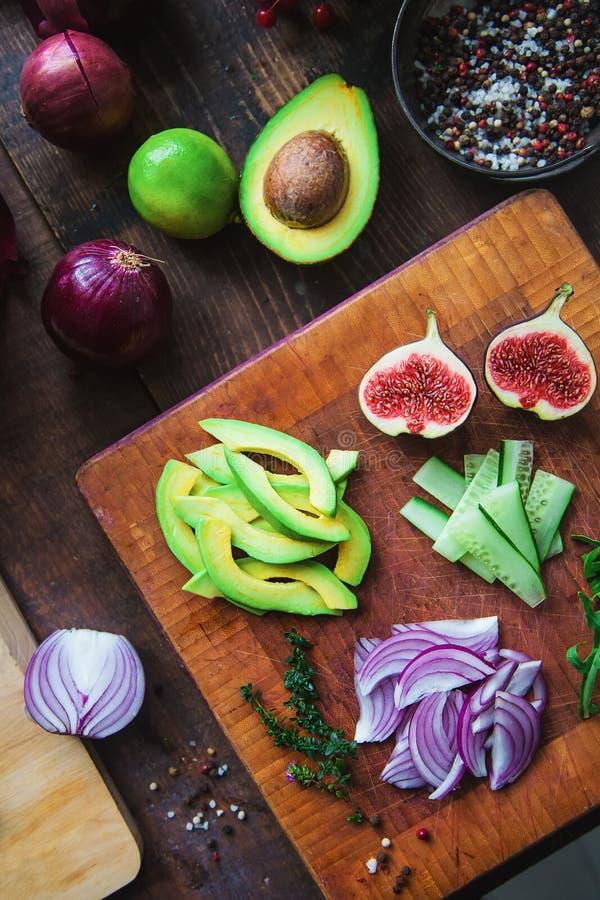 Figur, avokado, gurka, arugula, röd löken, timjan, kalk, kryddor på ett skärande träskikt - salladsingredienser arkivbild