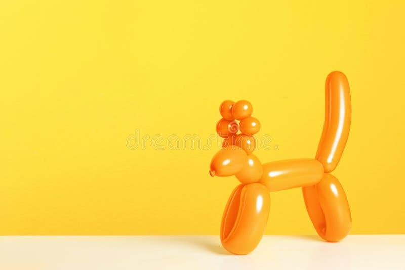Figura animal feita de modelar o balão na tabela contra o fundo da cor fotografia de stock royalty free