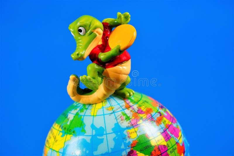 A figura crocodilo do brinquedo das crianças joga uns pires de voo no globo da terra O brinquedo é um modelo reduzido de um imagi fotos de stock royalty free