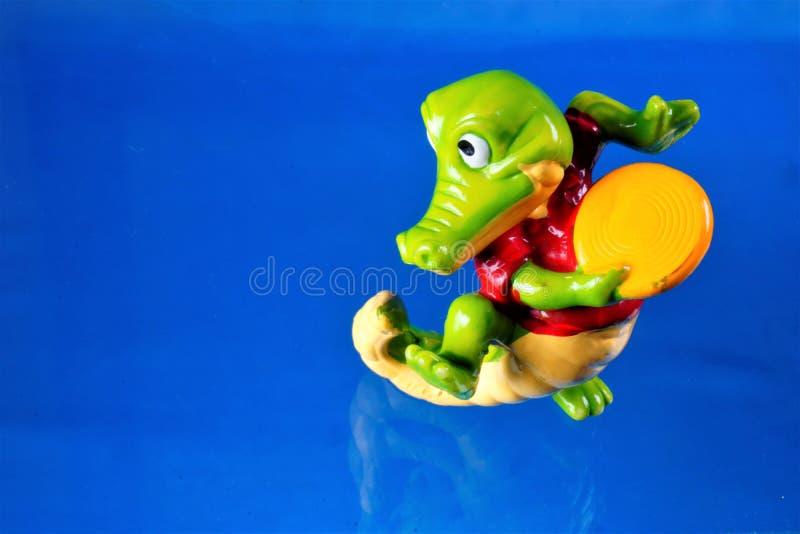 Figura crocodilo do brinquedo das crianças que joga em uns pires de voo O brinquedo é um modelo reduzido de uma criatura imaginár imagens de stock royalty free