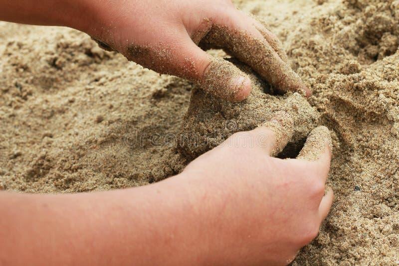Figura da areia na forma de um coração com mãos de uma criança fotos de stock
