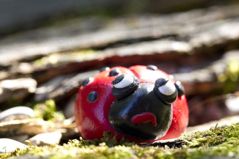 Figura da argila do joaninha que olha cética fotografia de stock