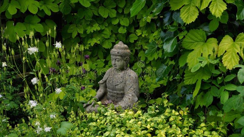 Figura da Buda em um jardim da mola imagem de stock