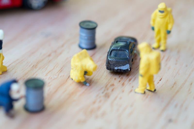 Figura da equipe do sapador-bombeiro na posi??o do terno do hazmat ao lado do carro imagens de stock