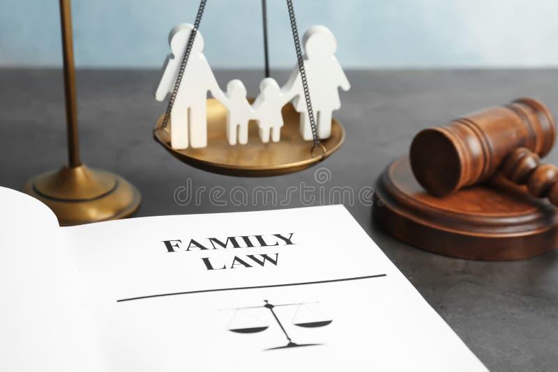 Figura da família, escalas de justiça, martelo e livro imagem de stock